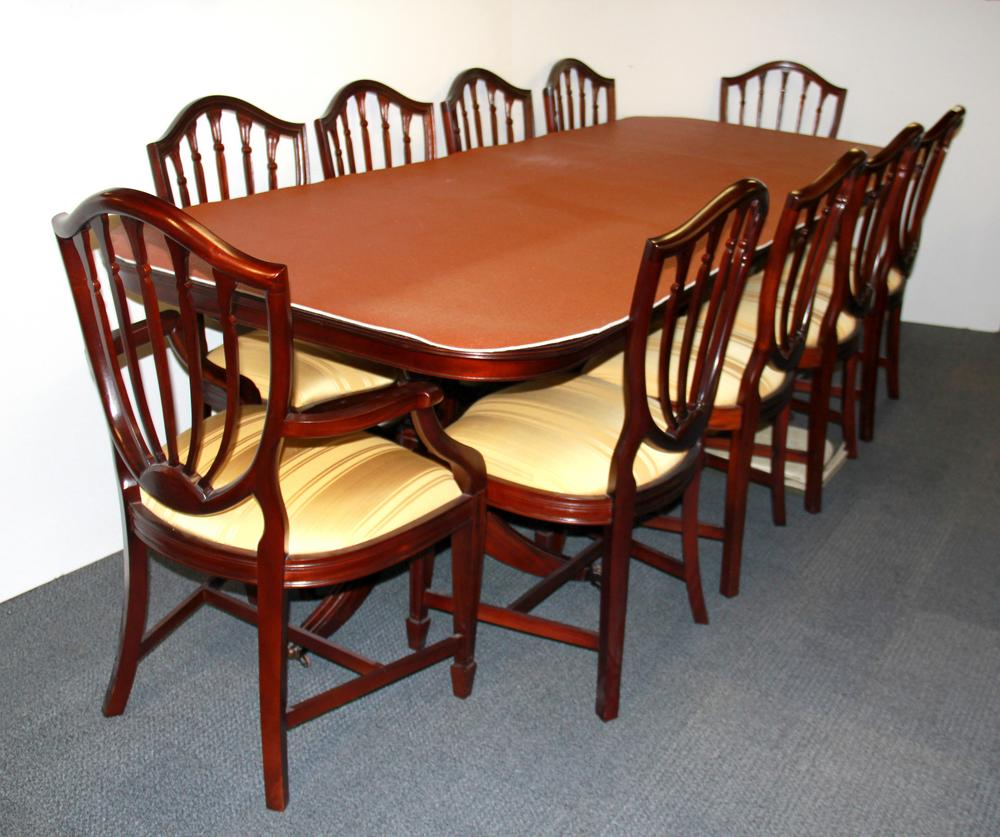 A large contemporary extending mahogany dining table and ten chairs with  full size heat protector, table L. 265cm W. 100cm.