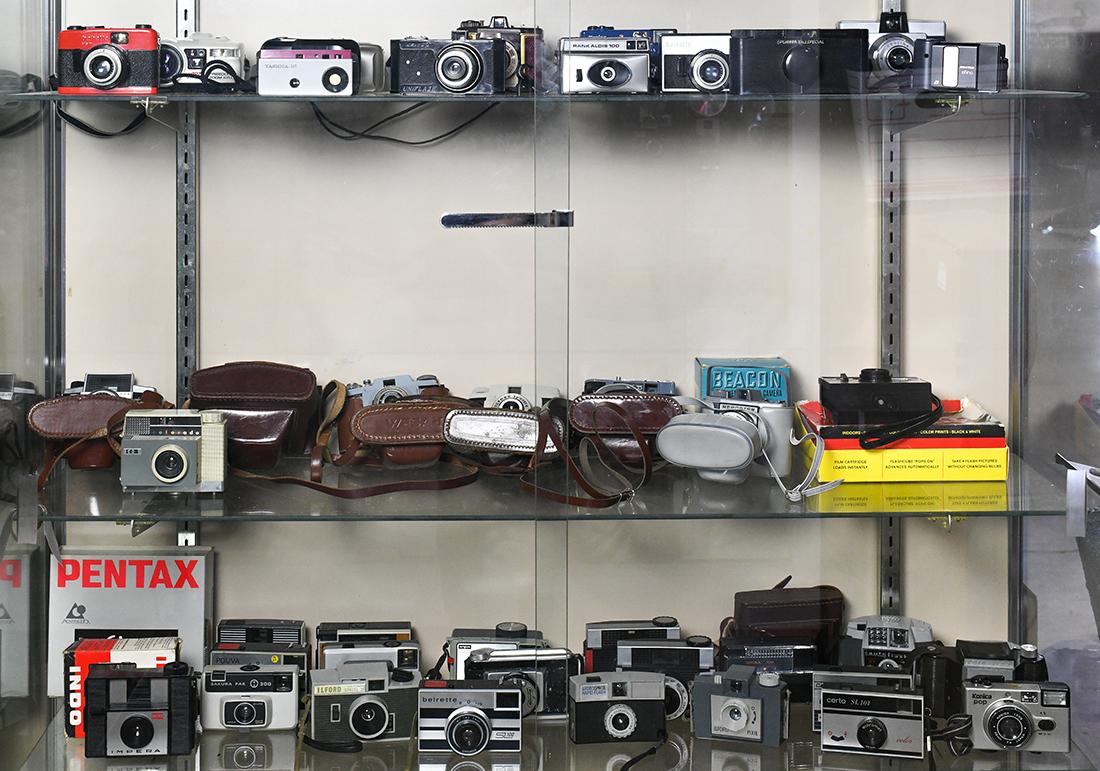 Three shelves of vintage and retro plastic cameras